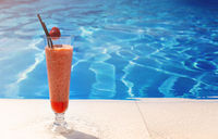 Glass with a bright red cocktail on the table by the pool with copy space