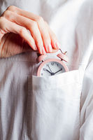 Woman with alarm clock spends time carefully