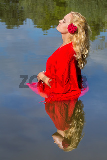 Blonde woman in red stands in natural water