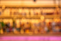 Blurred creative background of restaurant bar with pink desk space.