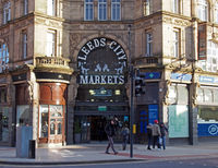 people walking past the entrance to Leeds city markets, a historic covered market building in Leeds, west yorkshire