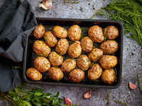 Tasty fresh homemade baked potatoes served on a metal tray. With various herbs, butter, garlic, salt