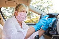 Putzkraft reinigt Armaturenbrett in Mietwagen wegen Coronavirus