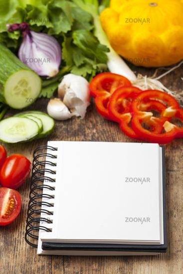 Notizbuch mit Gemüse auf Holz