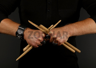 Man hands with broken drumsticks over black
