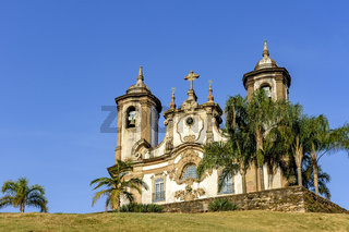 Ancient and historic church in 18th century colonial architecture with towers and palms at Ouro Preto city
