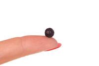 TCM herbal pill on woman finger.