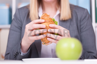 Woman at the office eating food in her break. Business