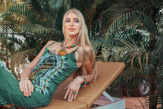 Young blonde woman in green dress relaxing at tropical resort