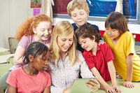 Schüler und Lehrer schauen auf Tablet PC