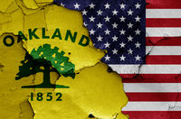 flags of Oakland and USA painted on cracked wall