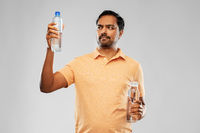 indian man comparing water in different bottles
