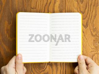 Hands open empty notebook on wooden desk. top view, copy space