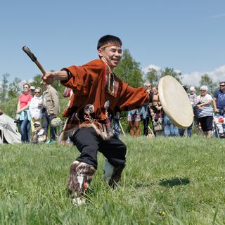 Man in clothes indigenous people of Kamchatka dancing with tambourine