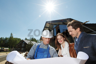 Foreman and couple hold blueprint