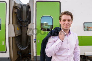 Young handsome businessman in front of train at railway station