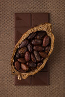 Chocolate bar and cocoa beans on dark background.
