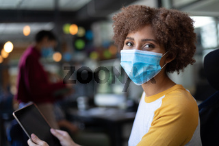 Portrait of mixed race woman wearing face mask using tablet in casual office