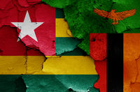 flags of Togo and Zambia painted on cracked wall