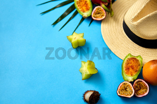 straw hat and exotic fruits on blue background