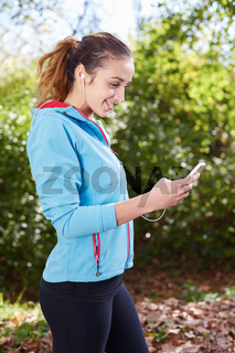 Young Sporty Woman Taking a Selfie at Park. She is Looking at Smart Phone