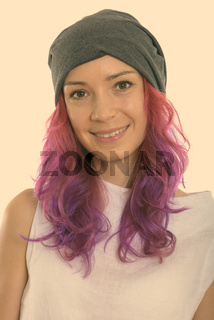 Face of young happy woman smiling with pink hair and wearing hat