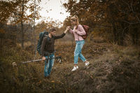 Hiking in nature. Young Man and Woman backpackers descend from the slope holding hands and holding hiking poles in their hands. Tourists with backpacks walk through the autumn forest. Support concept