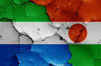 flags of Sierra Leone and Niger painted on cracked wall