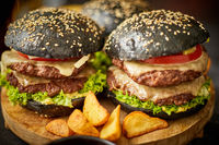 Appetizing black hamburgers and fried potato