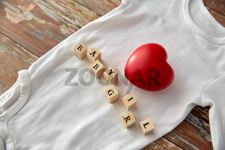 baby bodysuit with red heart on wooden table