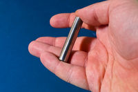 Tungsten rod in the hand. A piece of tungsten for experiments