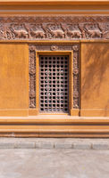 Recessed closed wooden door in ornamental stone wall outside of old building