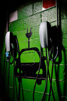 Electric vehicle charging station, free parking place green colored painted on wall symbol close up, no people, vertical image