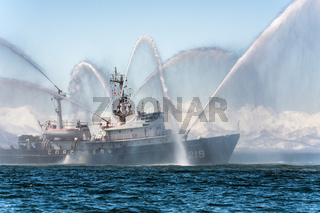 Firefighting ship spraying water on sea for supporting emergency case of fire