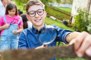Junge untersucht neugierig ein Stück Baumrinde