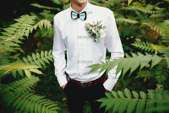 Groom in white shirt with bowtie and boutonniere. Hands in pockets