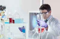 Researcher performing scientific experiment in chemical laboratory.