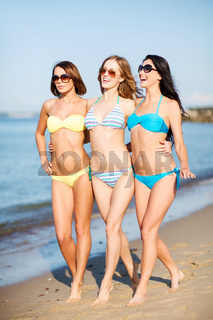 girls in bikini walking on the beach