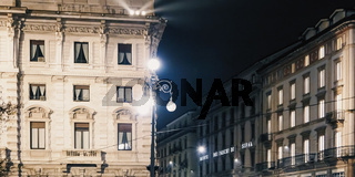 Historical buildings on the city center streets of Milan in Lombardy region in Northern Italy at night, classic European architecture
