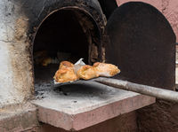 Cooked Cypriot Easter cheese pies Flaounes on a clay oven