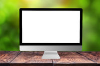 Mockup computer screen on wooden table against a blurred background.