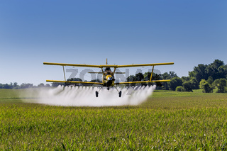 Yellow Crop Duster Spraying Pestisides On Crops