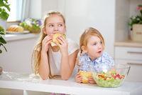 Zwei Kinder essen Brötchen in der Küche