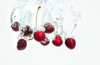 Red Cherries splashing into water against white background
