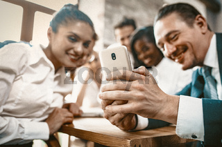 Diverse Team Of Employees Are Watching Photos In Mobile Phone