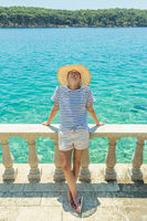 Rear view of woman wearing straw summer hat ,leaning against elegant old stone fence of coastal villa, relaxing while looking at blue Adriatic sea, on Losinj island Croatia.