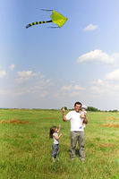 Happy father playing kite with children in meadow in sunny summer day