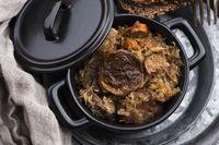 Traditional polish sauerkraut (bigos) with mushrooms and plums for christmas