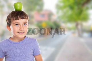Young boy child with an apple fruit on his head town copyspace copy space healthy eating