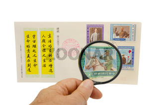 Old Chinese stamps under a magnifying glass.